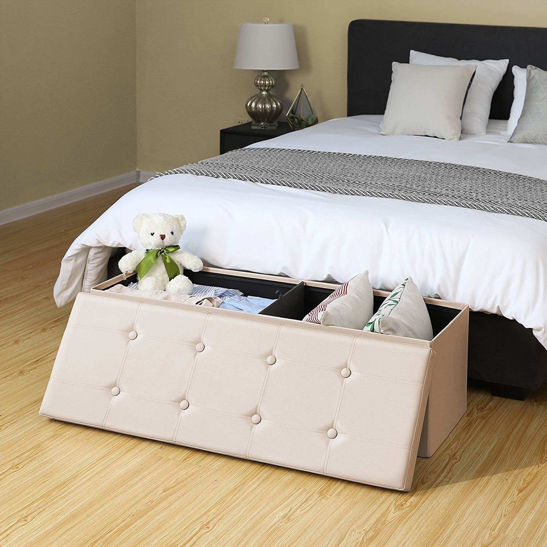 Retangular white storage bench with pillows and stuffed animals in it