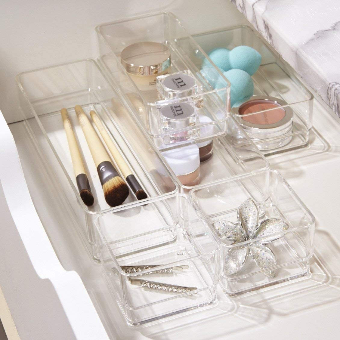 Clear plastic organizers with makeup and jewelry in them in a drawer