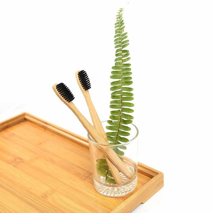 Two bamboo toothbrushes in a glass next to a leaf
