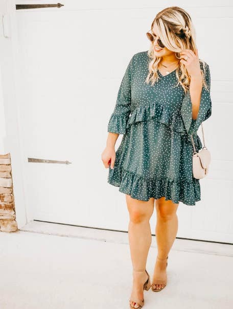 reviewer wearing the polka dot dress with a row of ruffles under the bust and along the hem