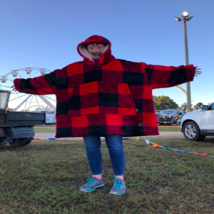 A reviewer wearing the red and black buffalo plaid version outside with jeans