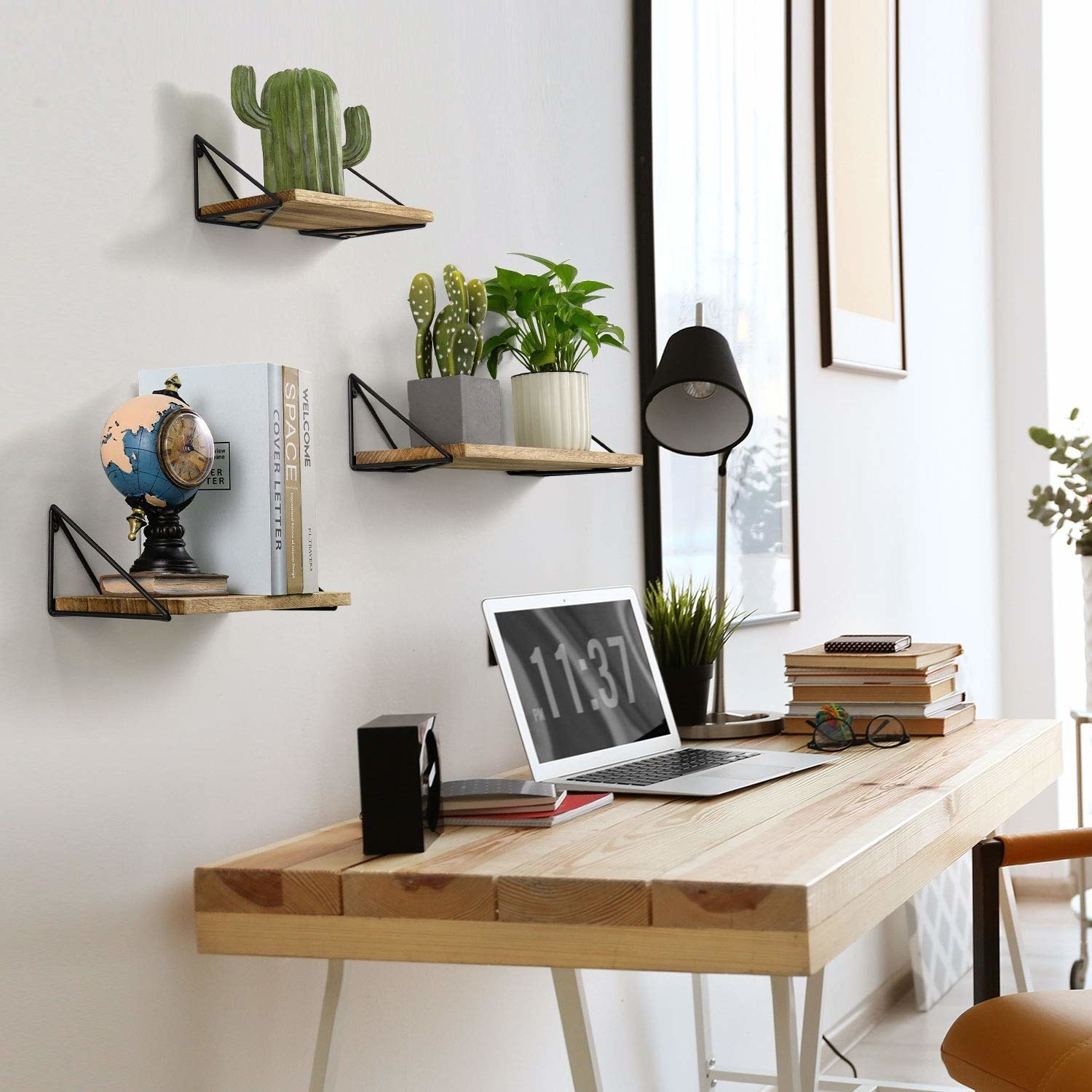 Set of three light wood floating shelves installed on a wall above a desk