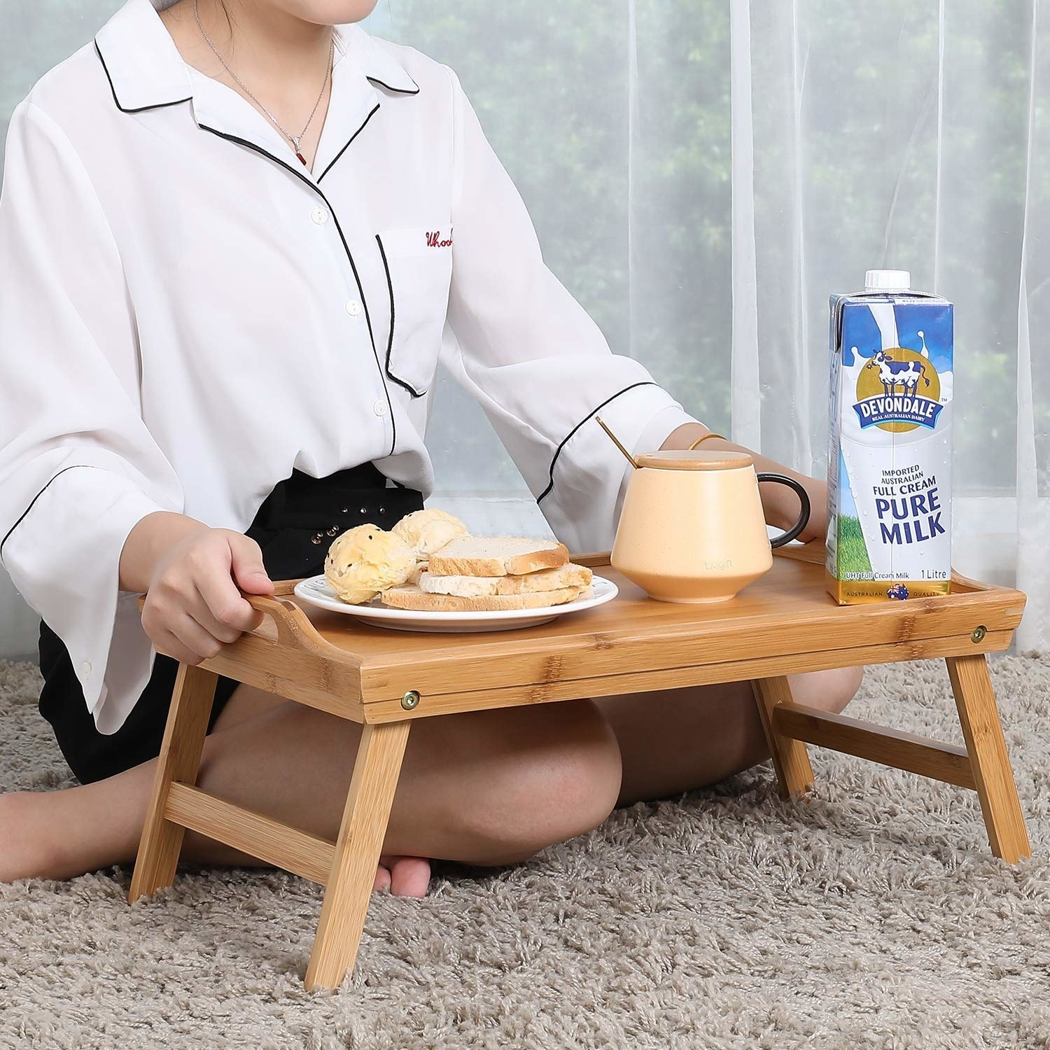 A model sitting on the floor with a wooden breakfast tray elevating food