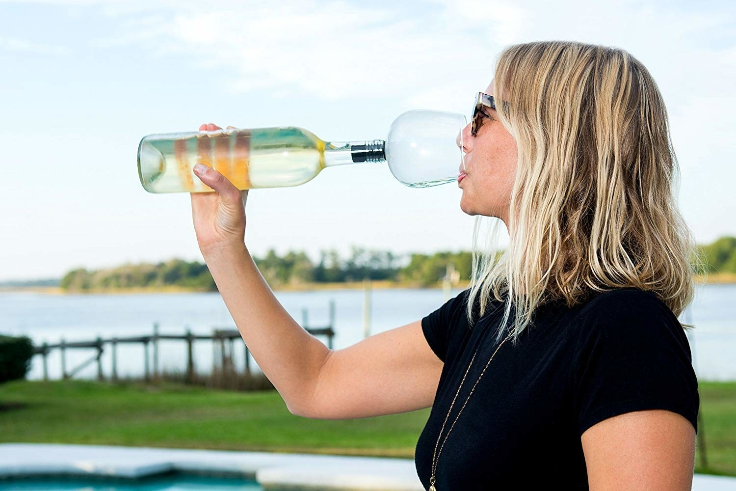 model drinking from the product, which is a wine glass that attaches straight to the top of the bottle