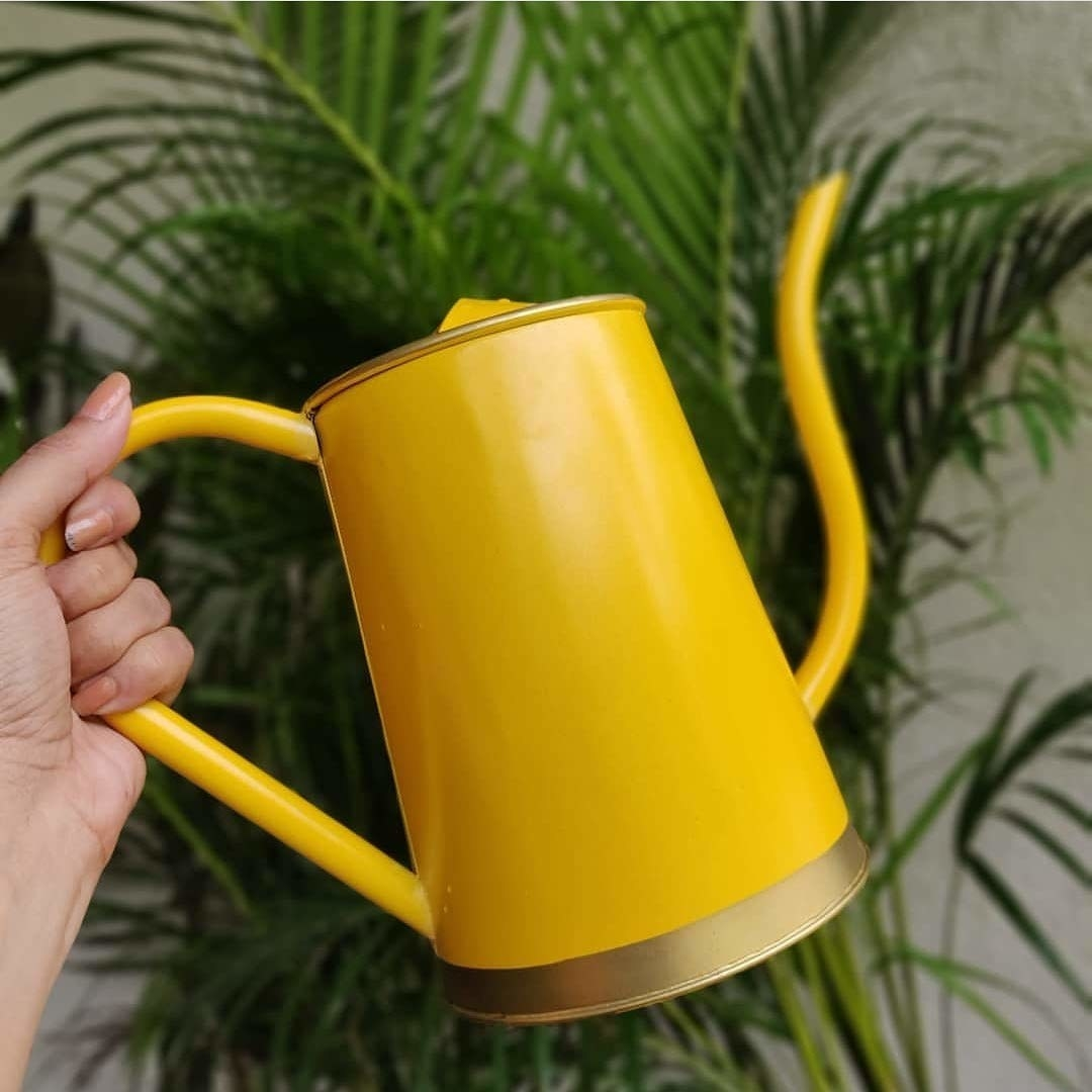A bright yellow watering can.