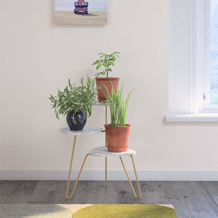 a one-piece plant stand with three marble platforms spread out for potted plants to sit on top of