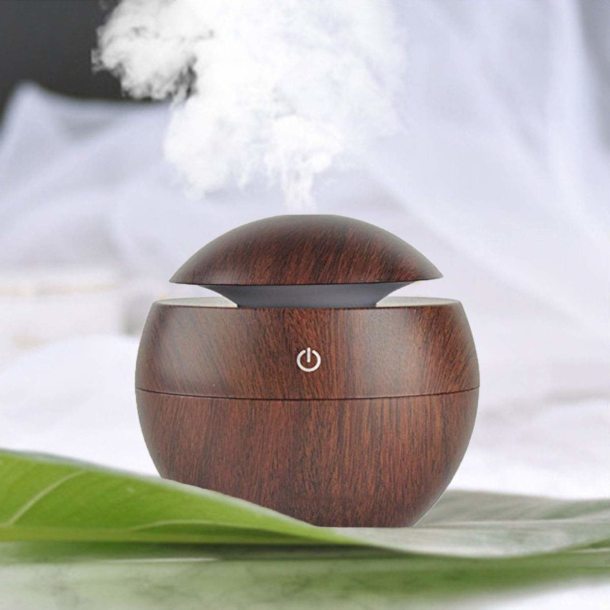 A brown diffuser on a table, releasing essential oils in the air