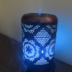 same essential oil diffuser with a blue glow