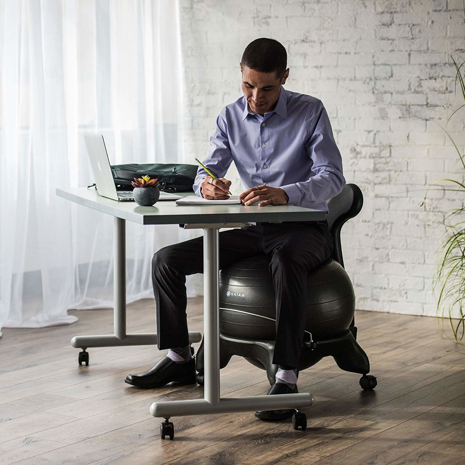 A person sitting on the chair and working at their desk.
