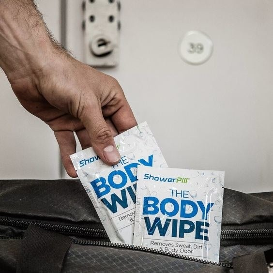 hand placing the body wipe in a gym bag