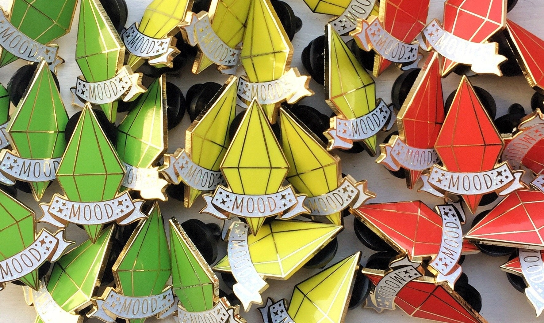 "green, yellow, and red plumbob pins with the word ""mood"" written across them"