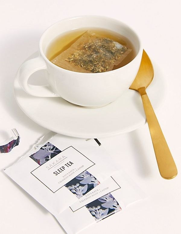 A lifestyle shot of the tea steeping in a cup with the open pouch beside it