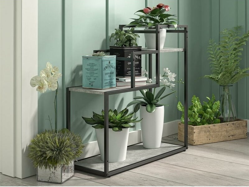 A three-level plant stand with a dark metal frame and marble-colored shelving