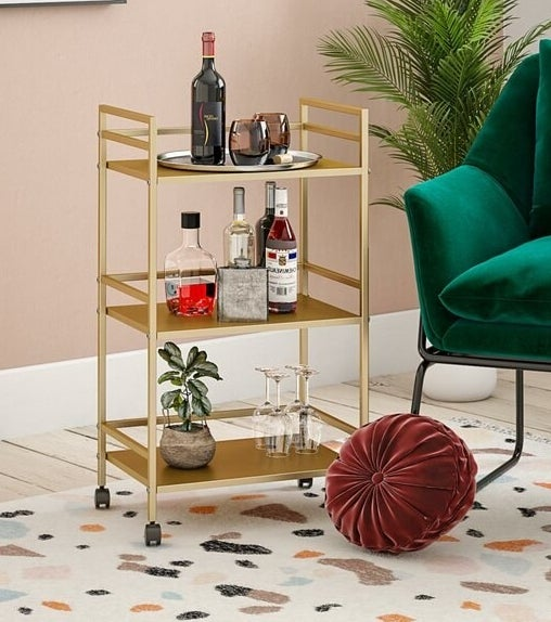 A gold metallic three-shelf bar cart on four caster wheels filled with bottles and glasses situated atop a colorful rug