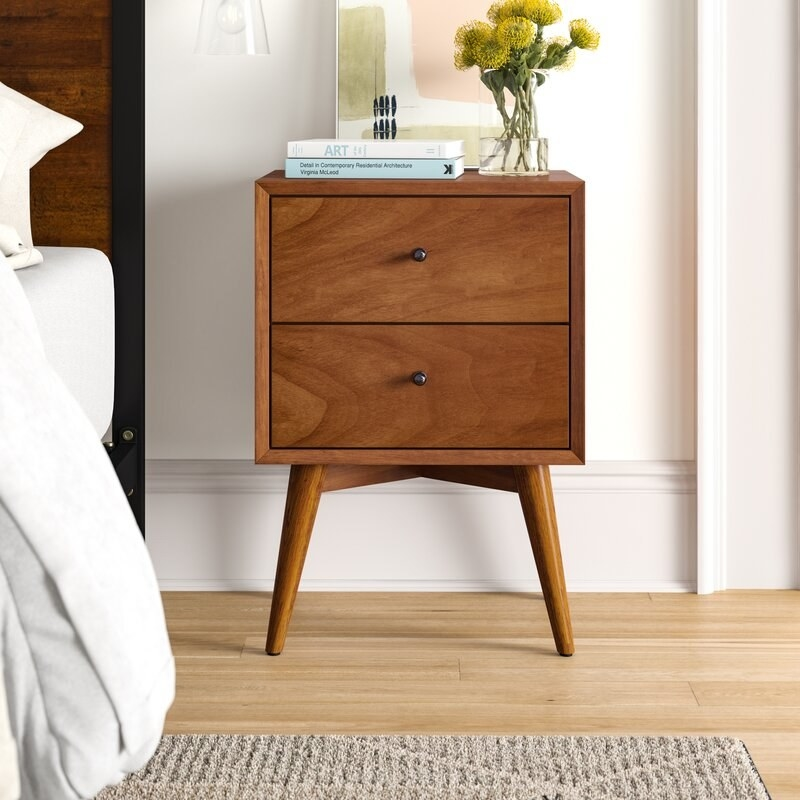 A walnut-colored square two-drawer nightstand with small round black drawer knobs