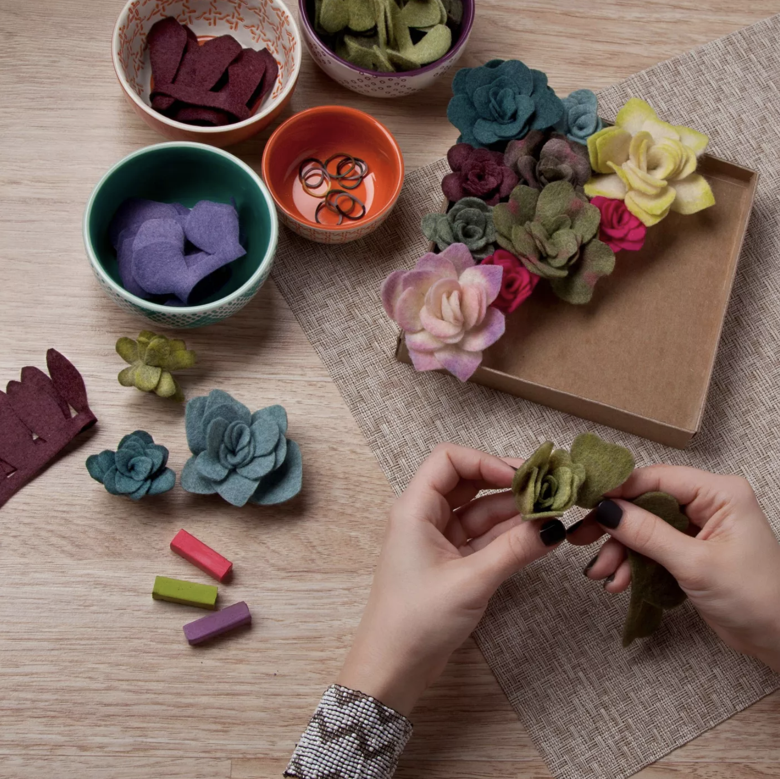 A model's hands holding green felt pieces that look like succulent leaves. More completed felt succulents are sitting near on a table near the hand.