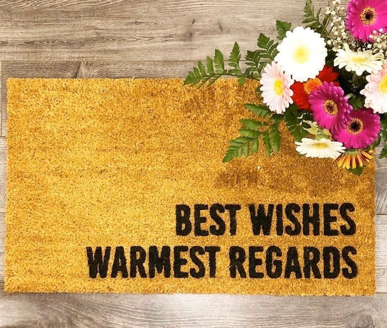 "The brown doormat with ""Best wishes warmest regards"" written on it in black letters"