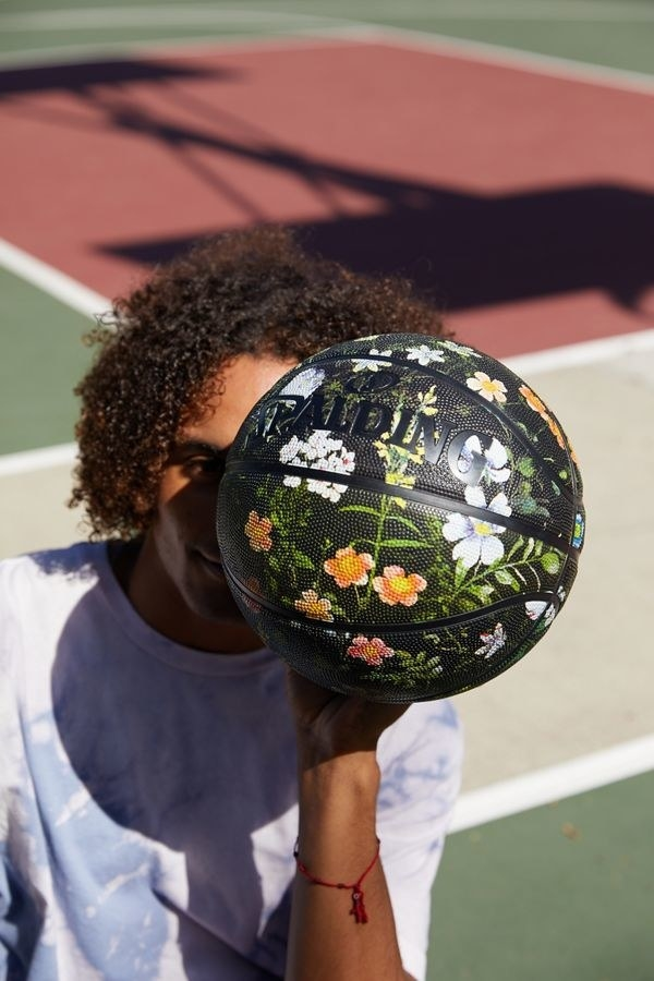 model holds black basketball with floral design