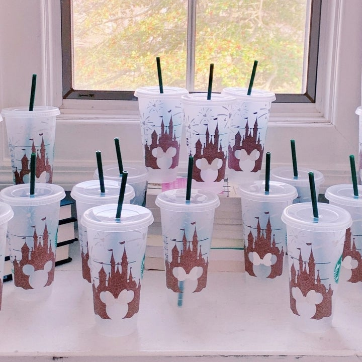 a bunch of cups with rose gold overlay of the castle and a cut out mickey in the middle