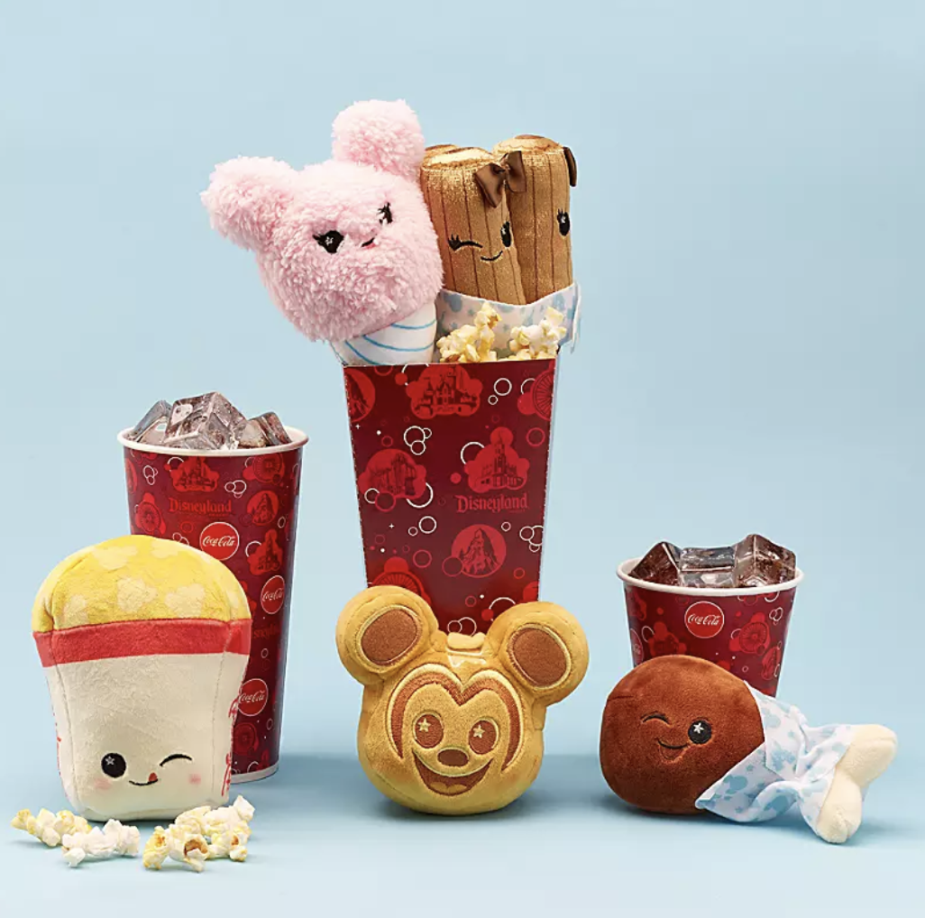 four small stuffed toys: a popcorn, a mickey waffle, a turkey leg, and a cotton candy. each have a happy winking face on it