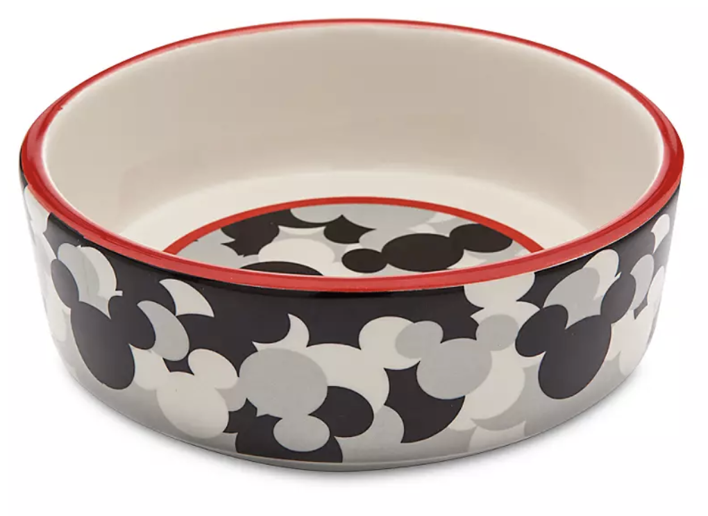 a round ceramic dog bowl with a black white and grey mickey design on it and a red accent around the edge