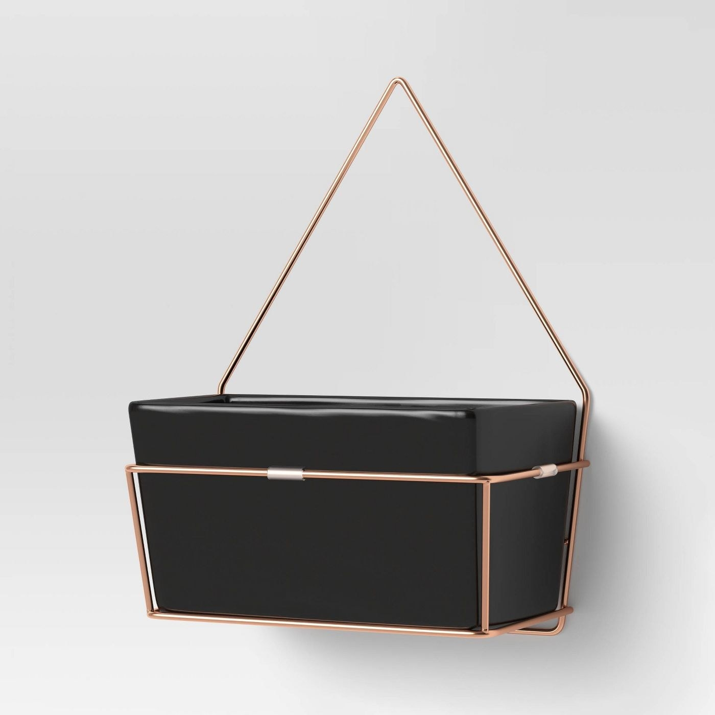 Black hanging box with minimalist rose gold hardware mounted against wall
