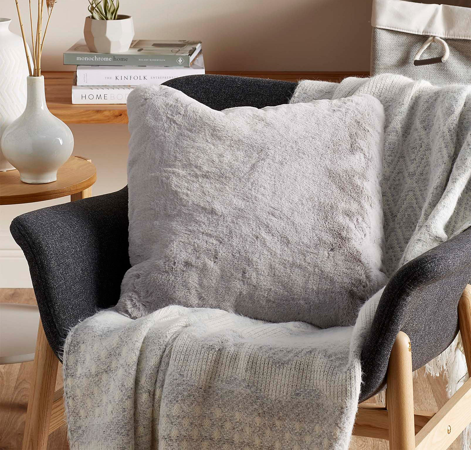 A fluffy throw pillow on a small chair with a blanket