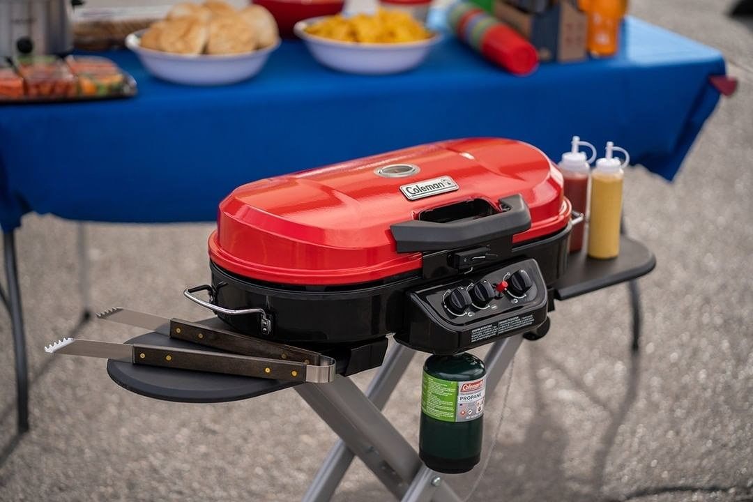 a red portable grill with two small platforms on each side, one has a pair of tongs on it while they other has bottles of ketchup and mustard