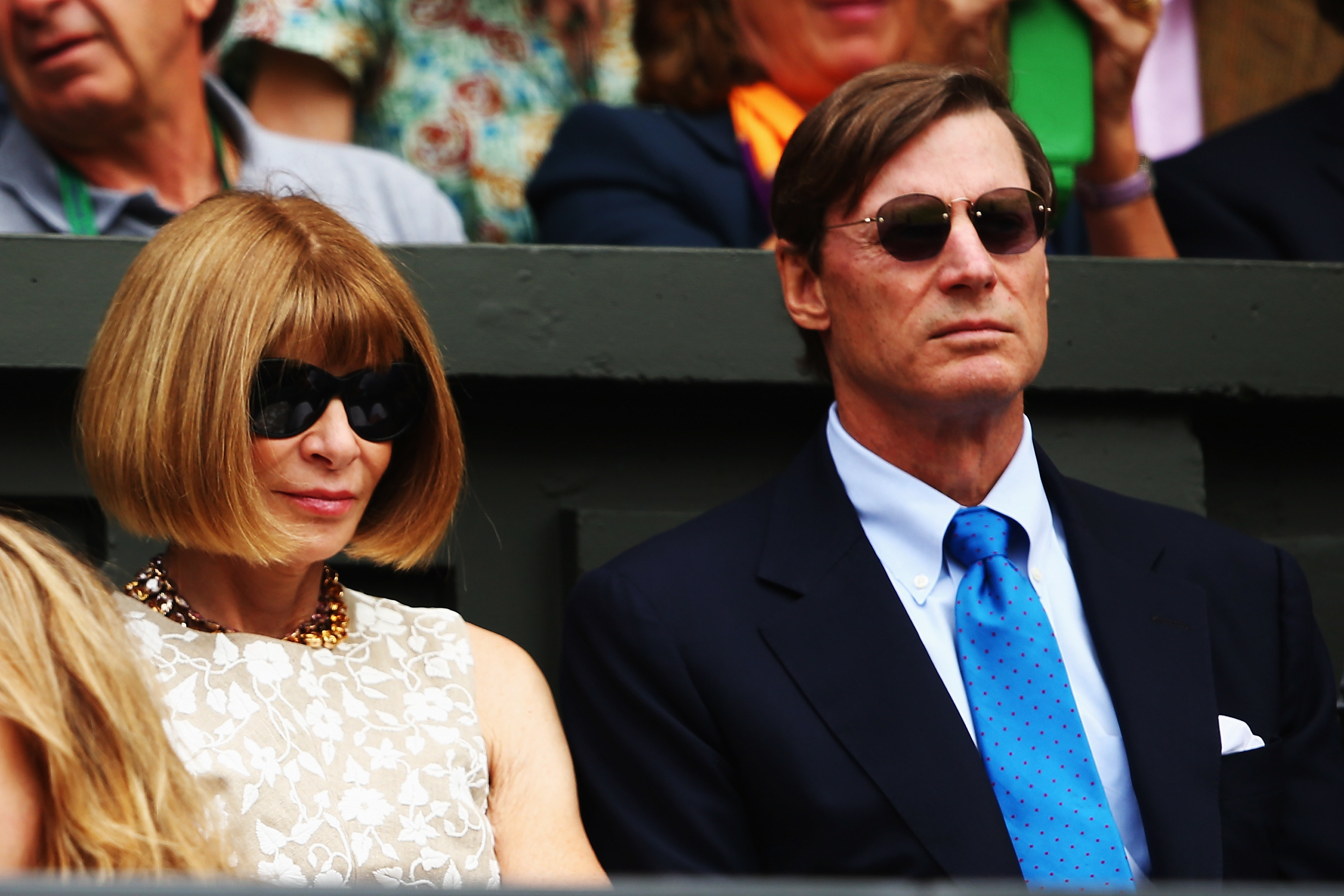 at a tennis match in glasses looking intimidating