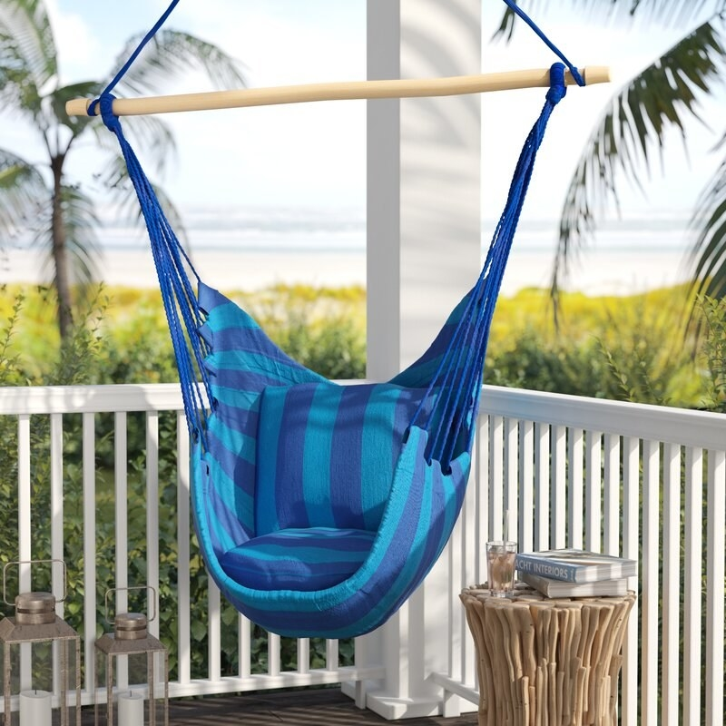 a blue and turquoise striped chair hammock hanging above a porch