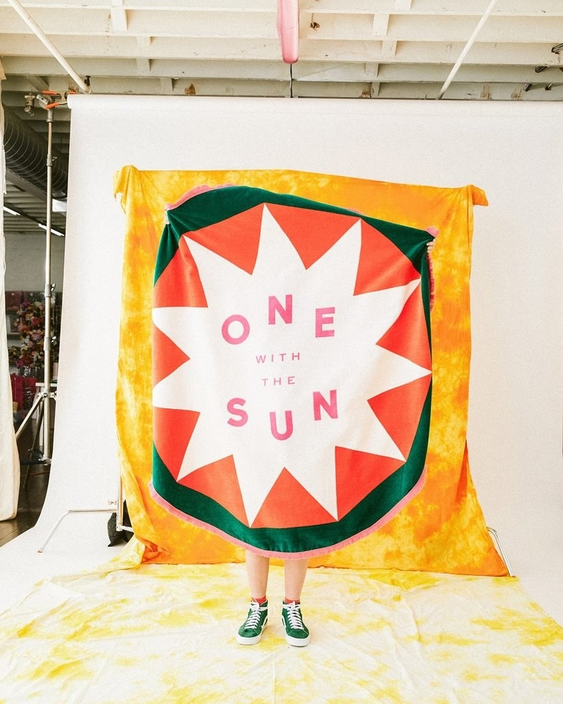 "a person holding up a bright yellow towel with a green circle around an orange circle around a white star with the words ""one with the sun"" in the middle in pink"