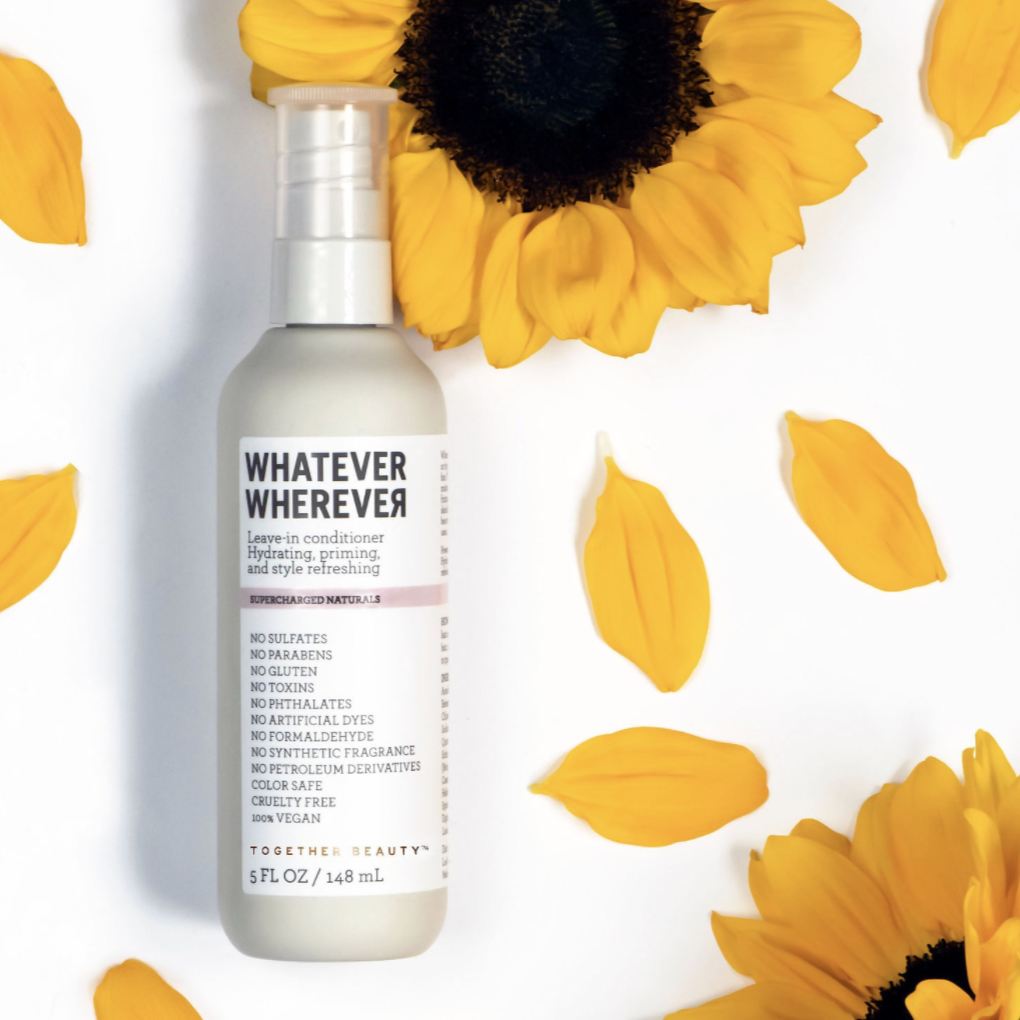 bottle of leave-in conditioner next to sunflowers