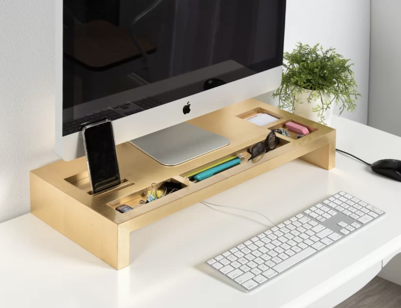the gold monitor stand with a computer on it, a phone, and compartments filled with pens, glasses, and other office supplies
