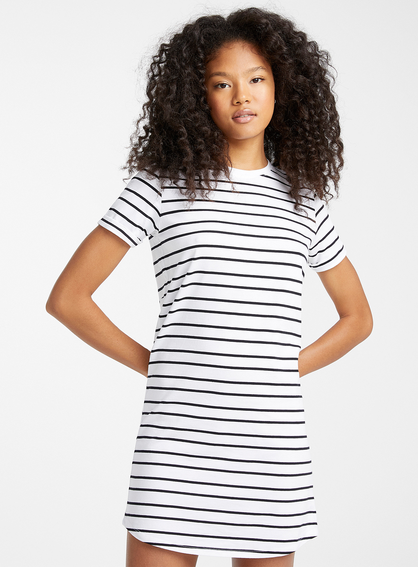 A person wearing a T-shirt dress with a striped pattern