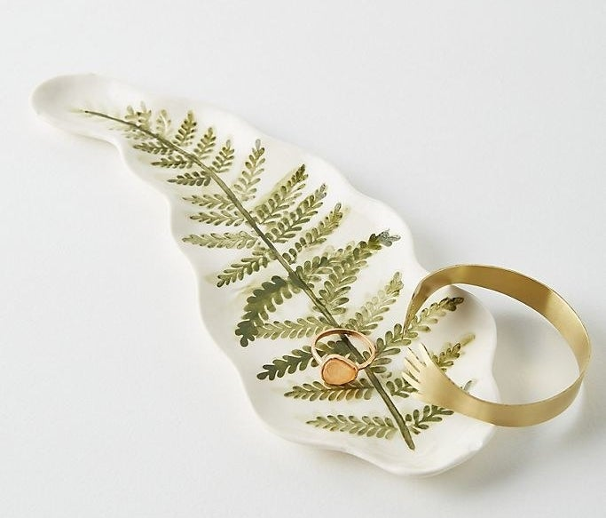 white dish painted with a fern leaf