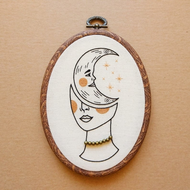 Half a person's face with necklace. The top half is a moon.