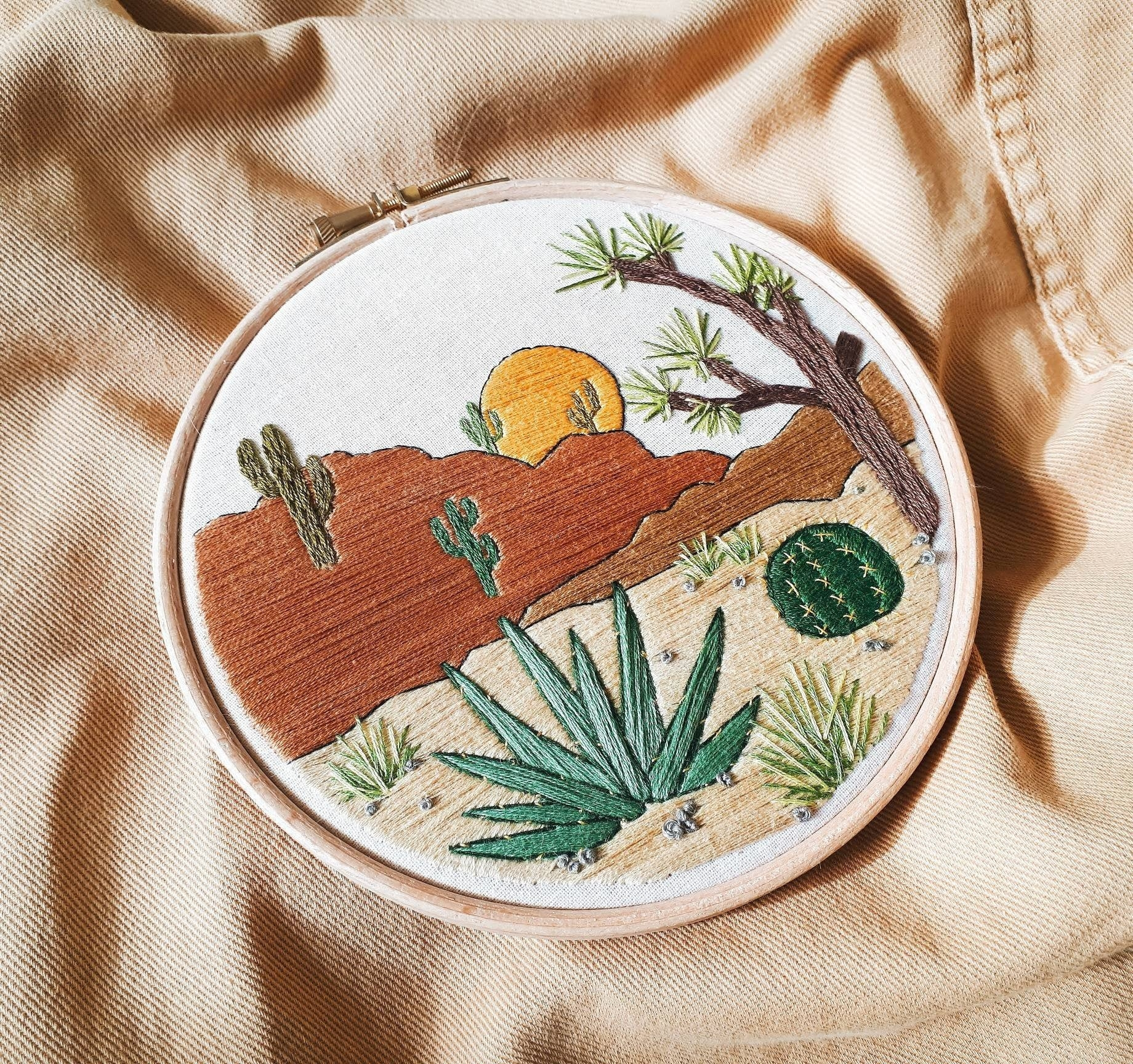 Desert scene with cacti, mountains, and a setting sun