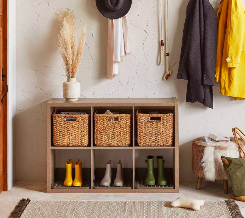 Six-cube wooden organizer filled with bins and rain boots