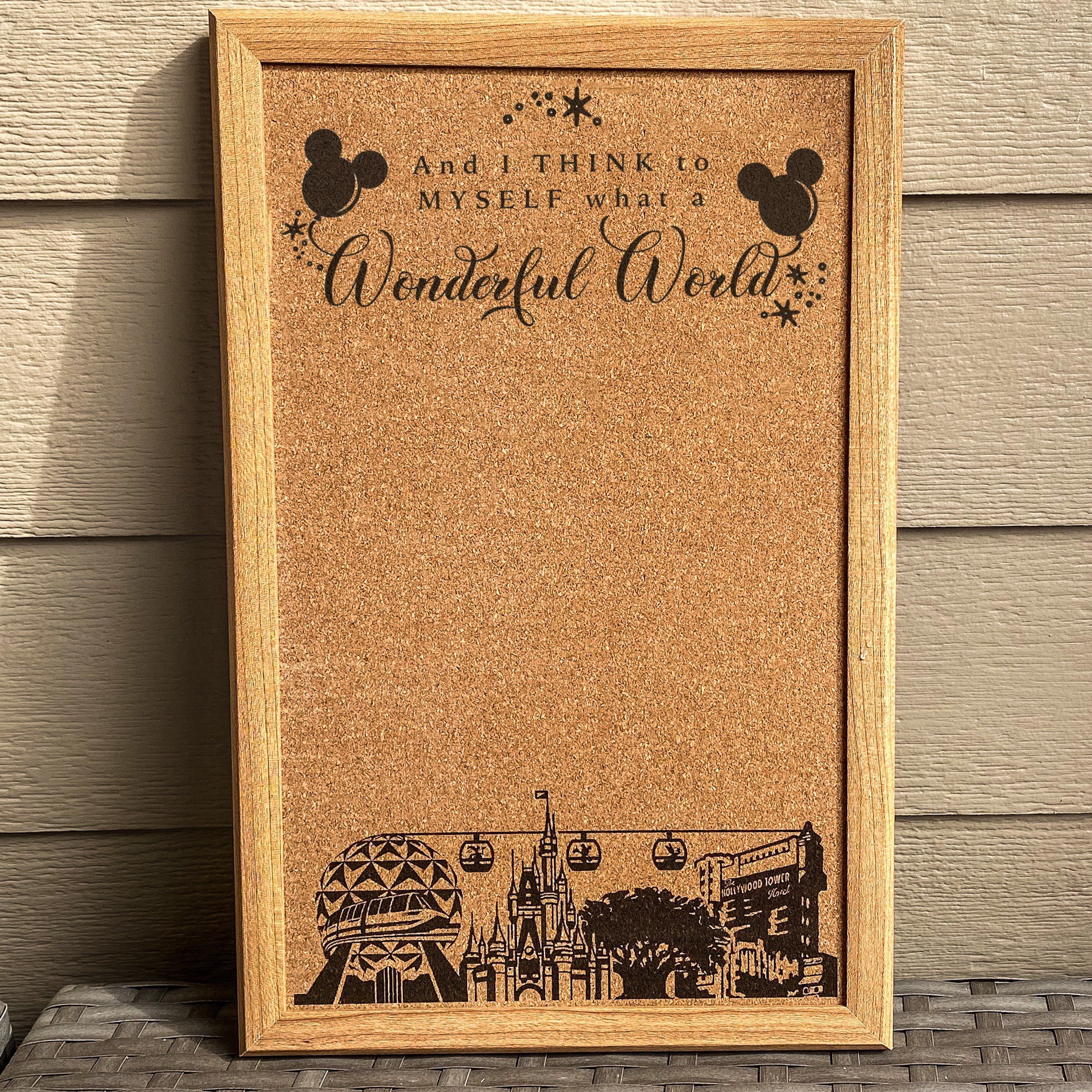"""a cork board with the four disney parks on it and the words """"and i think to myself it's a wonderful world"""""""