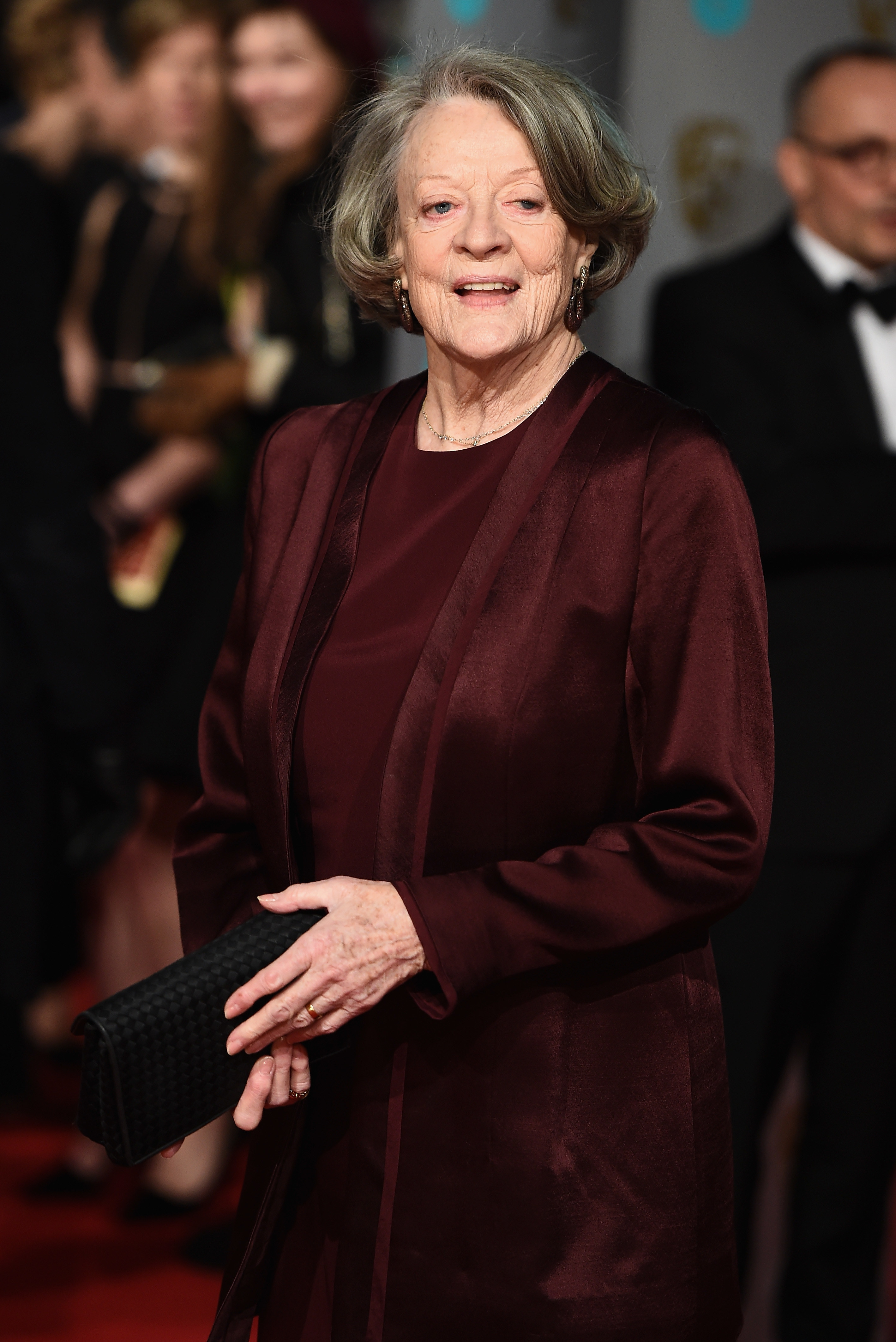 dame maggie smiling on a red carpet