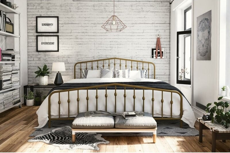 Golden bed frame made with vertical metal rails at the head- and footboards