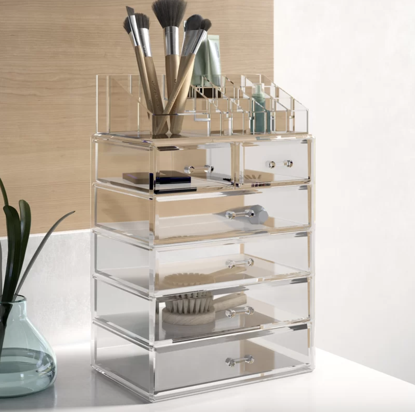 the clear organizer with some beauty products in the drawers and in the compartments on top