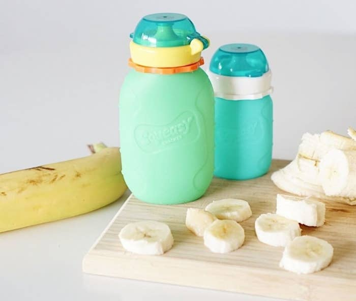 A small bottle with a lid placed on a wooden cutting board with chopped bananas on it