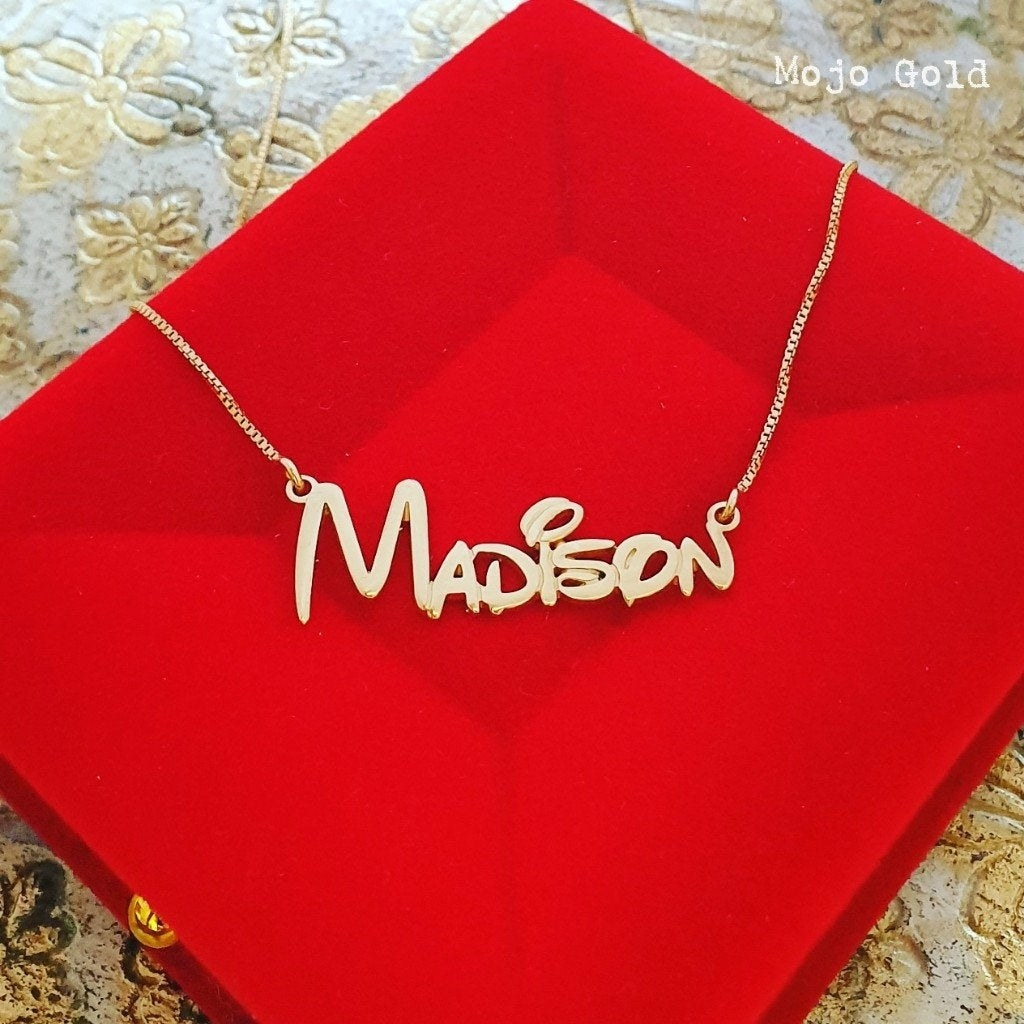 "a gold necklace that says ""madison"" in a disney font"