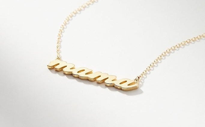 "gold chain necklace with the word ""mama"" written in gold"