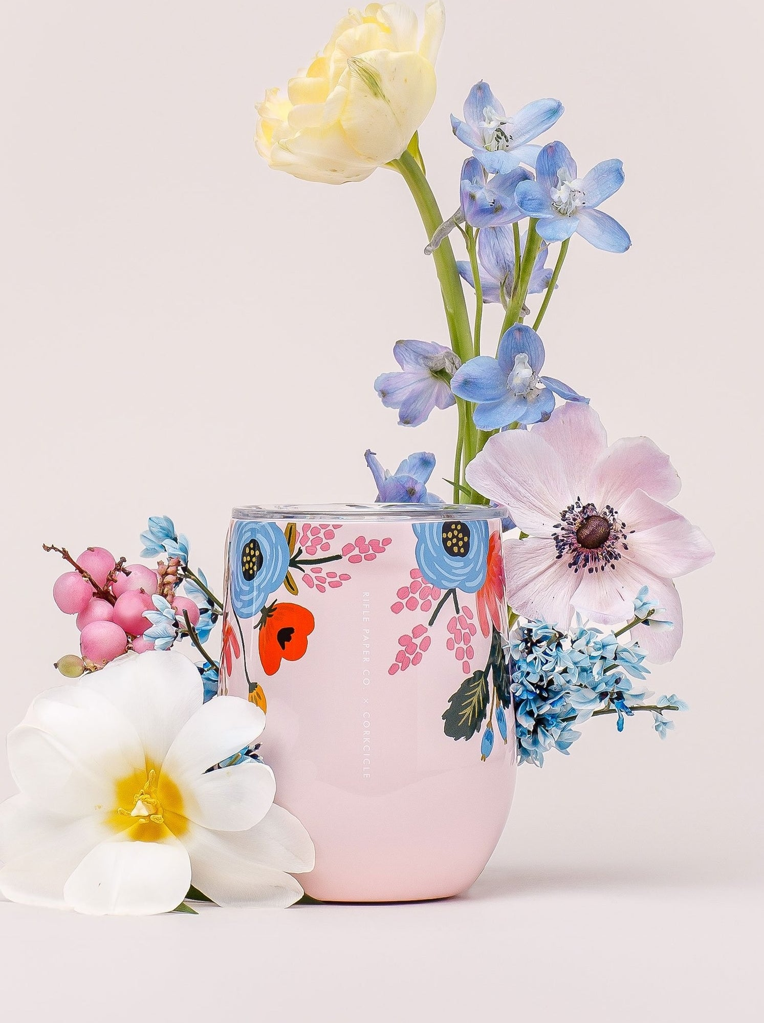 pink steamless wine glass with illustration of blue, red, and pink florals on it and a clear lid