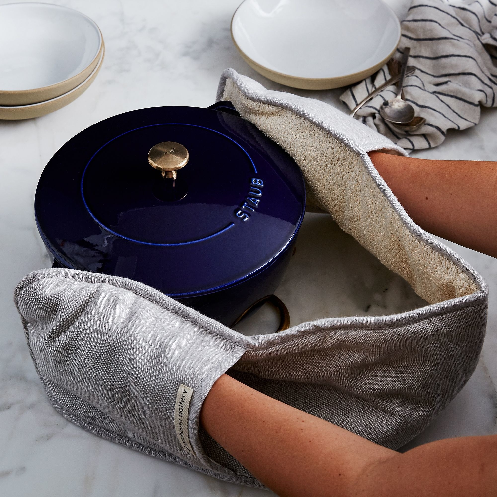 Wrap-around linen mitt being used to hold a Staub pot