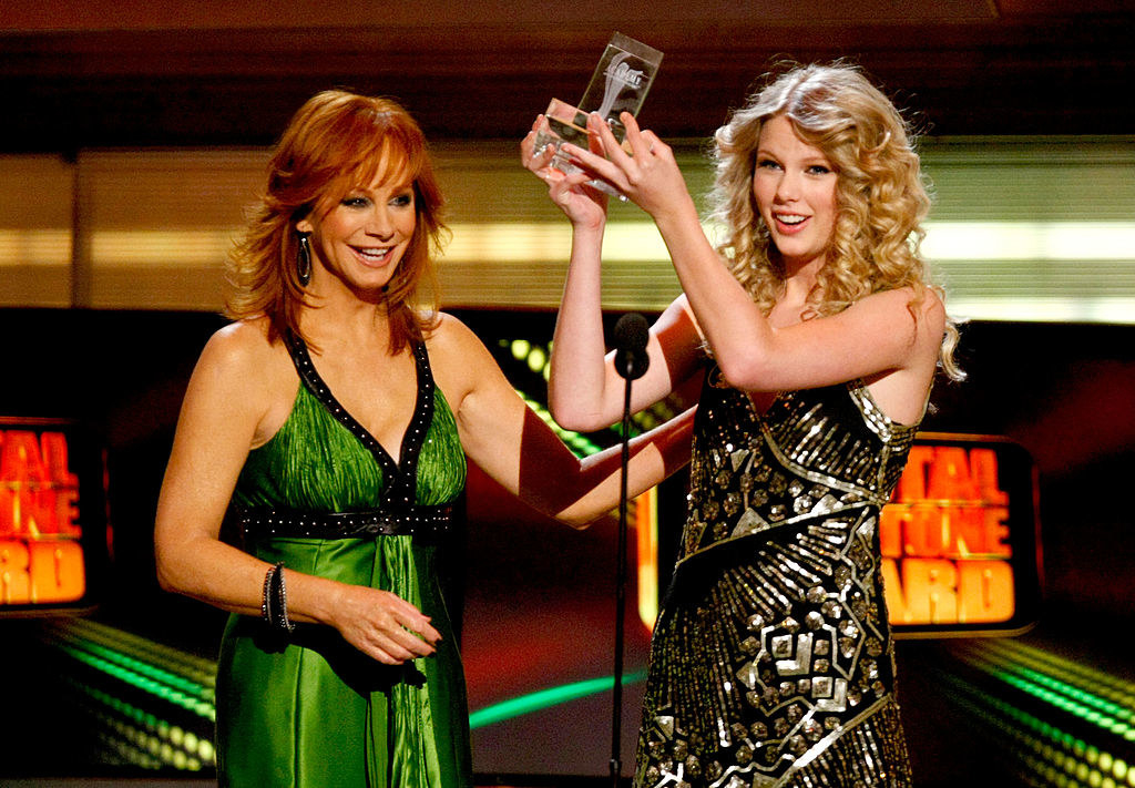 Standing with Reba McEntire onstage and holding a CMA
