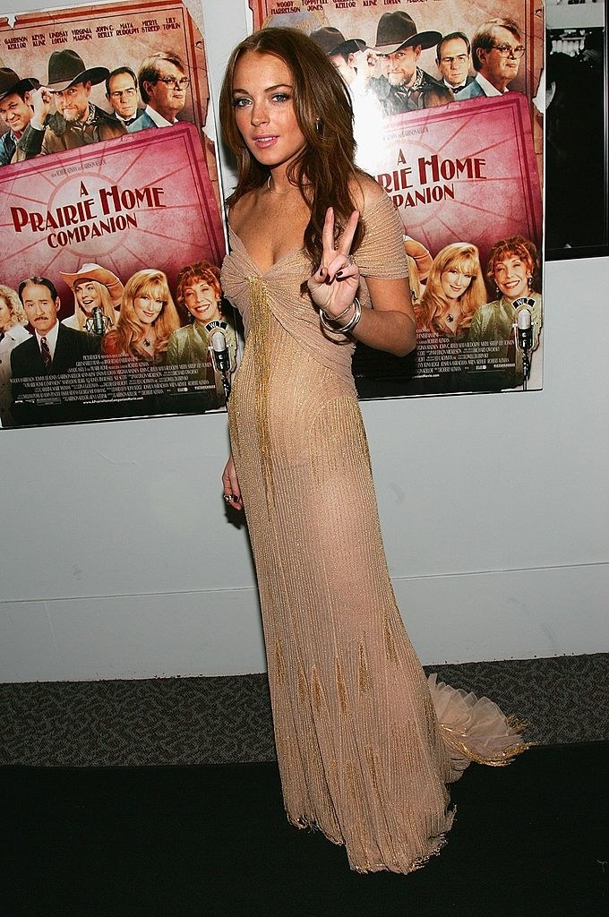 giving a peace sign, wearing a gown