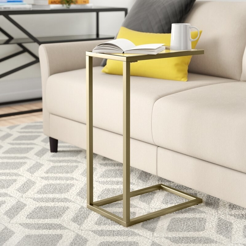 A thin, gold metal framed table with a glass top